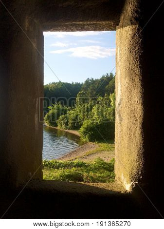 A view of a lake from an old stone castle window