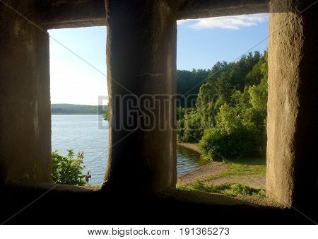 Stone castle windows overlooking isolated lake scene