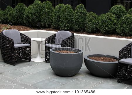 Arrangement of comfy chairs and tables in outdoor landscaped  garden.