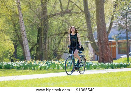 Portrait view of girl on bicycle wearing on black short dress. Young happy Woman riding along road on green spring  Park. Sporty young girl riding a bicycle on a sunny morning