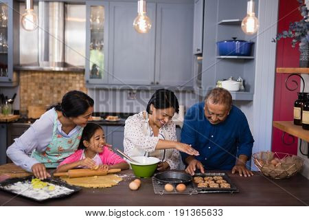 Happy multi-generation family preparing cookies in kitchen at home
