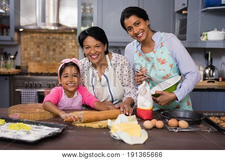 Portrait of smiling multi-generation family preparing food in kitchen at home
