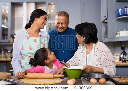 Multi-generation family standing together in domestic kitchen at home