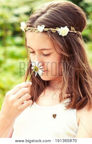 Carefree childhood. Happy boho style cheerful girl with floral headband on head and butterfly smelling camomile. Summertime multicolored outdoors vertical image.