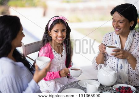 Portrait of smiling girl having breakfast with mother and grandmother at home