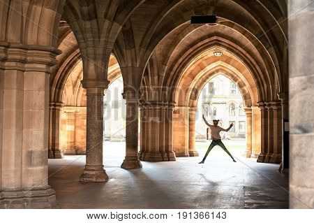 Silhouette of happy girl jumping high up in cloisters of Glasgow University. Scotland. Europe. Summertime outdoors image.
