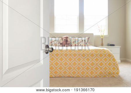 White door opened to sunny blurred defocused bedroom with big bed and windows in background in yellow and beige colors.
