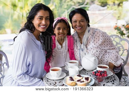 Portrait of smiling multi-generation family sitting together by breakfast table at home