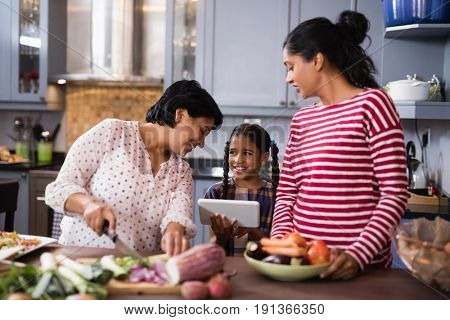 Happy multi-generation family preparing food while standing in kitchen at home