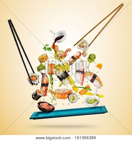 Flying sushi pieces served on wooden plate, separated on colored background. Many kinds of popular sushi food with chopsticks. Concept of flying asian dish with ingredients