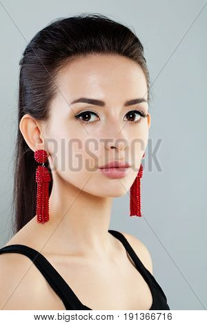 Pretty Woman with Makeup Dark Hair and Red Earrings