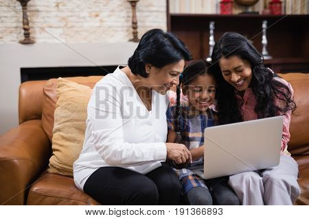 Happy multi-generation family using laptop together while sitting on sofa at home