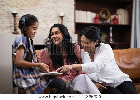 Happy multi-generation family using digital tablet while sitting together on sofa at home