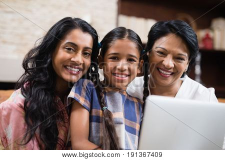 Portrait smiling multi-generation family with laptop at home