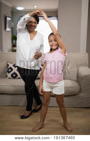 Portrait of smiling girl dancing with grandmother at home