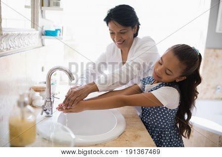 Grandmother and granddaughter washing hands at bathroom sink