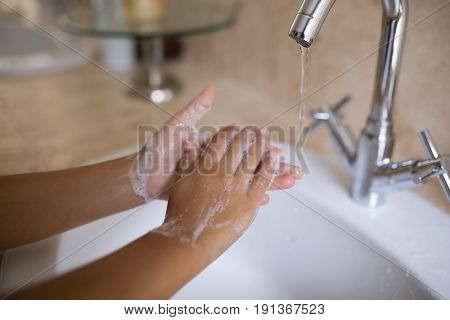 Cropped hand of girl washing hands at bathroom sink