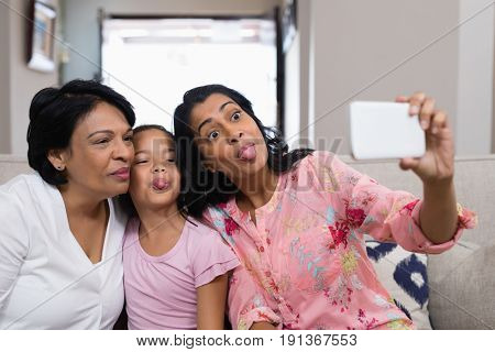 Happy multi-generation family taking selfie while making faces together at home