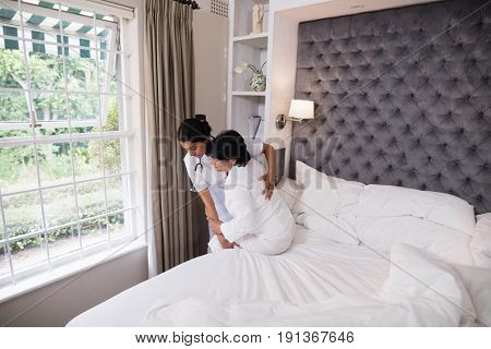 Nurse helping female patient on bed at home