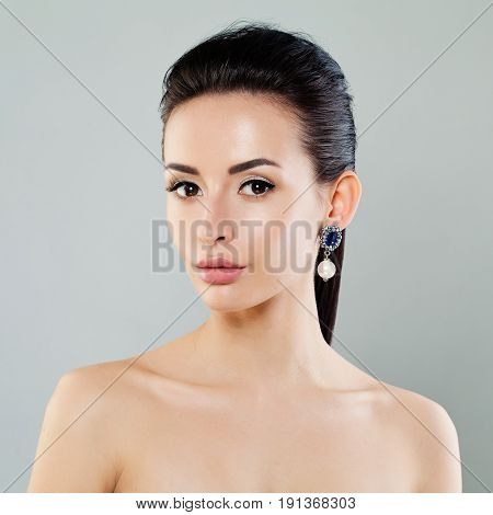 Young Beauty. Perfect Model Woman with Makeup and Earrings