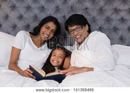 Portrait of smiling multi-generation family with book resting on bed at home