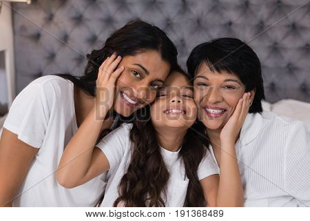 Portrait of smiling multi-generation embracing on bed at home