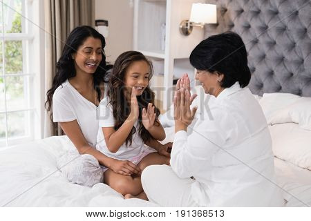 Happy multi-generation family playing patty cake on bed at home