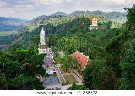 Buddhist monastery in beautiful tropical valley with tall statues of Guanyin and Buddha