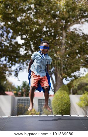 Full length of boy in superhero costume jumping on trampoline