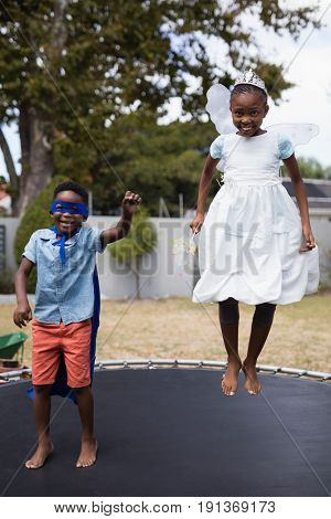 Full length of siblings in costumes jumping on trampoline at lawn