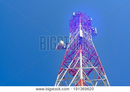 Mobile phone communication antenna tower with satellite dish on blue sky background Telecommunication tower soft tone