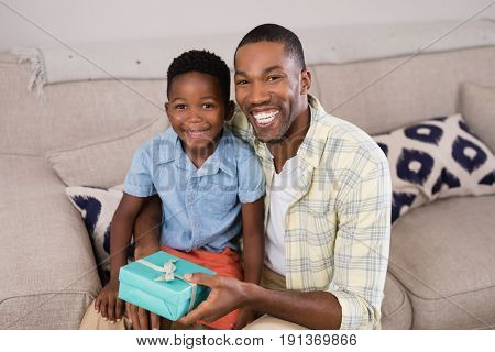 Portrait of smiling father and son with gift box sitting on sofa at home
