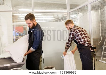 manufacture, business and people concept - men with bags weighing and pouring malt to mill at craft brewery or beer plant