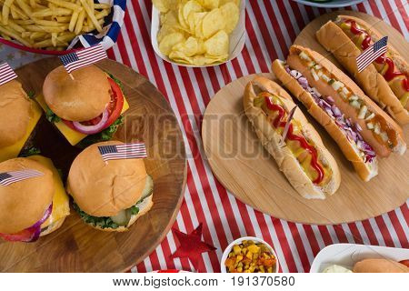 Close-up of hot dogs and burgers on wooden table with 4th july theme