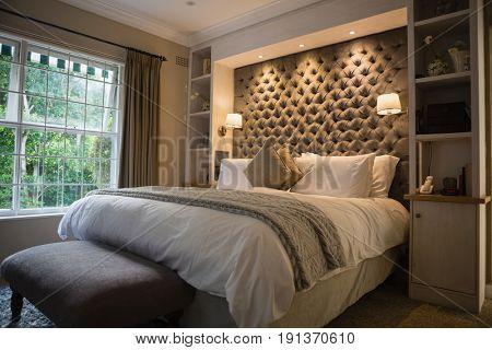 Illuminated neat bedroom at home