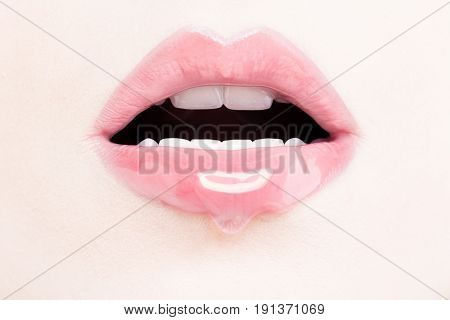 Female Lips with Pink Lip Gloss. Wet Lips with Makeup and Lip Gloss Drop