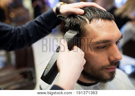 grooming, hairstyle and people concept - man and barber or hairdresser hands with trimmer cutting hair at barbershop