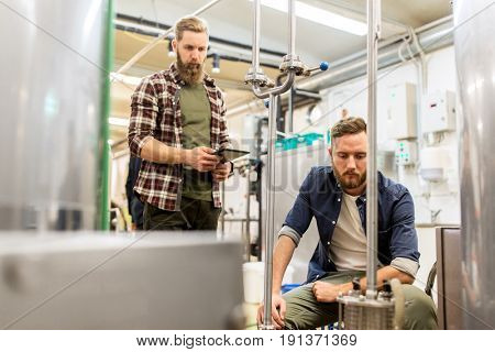 alcohol production, business and people concept - men with tablet pc computer at craft beer brewery filter