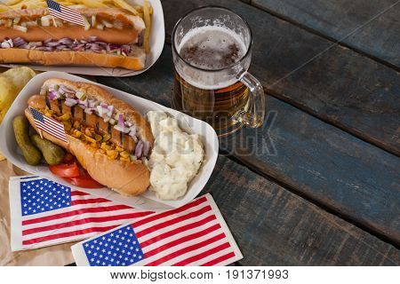 Overhead of hot dog and glass of beer with american flag on wooden table
