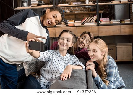 Happy Multicultural Teenagers Group Taking Selfie On Smartphone And Sitting On Sofa At Home, Teenage