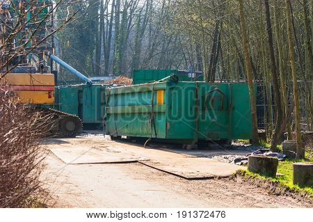 Excavator and green container on a construction site in the forest.