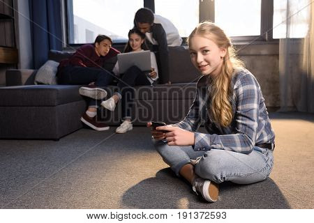 Smiling Teenage Girl Sitting On Floor And Using Smartphone With Friends Using Laptop Behind