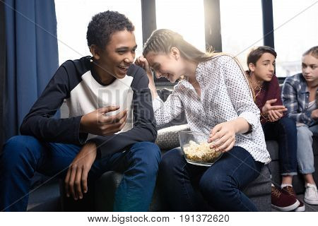 Happy Teenagers Sitting On Sofa And Eating Popcorn From Bowl Indoors, Teenagers Having Fun Concept