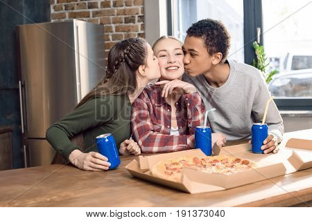 Side View Of Friends Kissing Smiling Teenage Girl's Cheeks, Eating Pizza At Home Concept