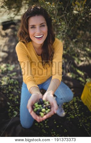 Portrait of smiling woman showing olives while crouching on field at farm