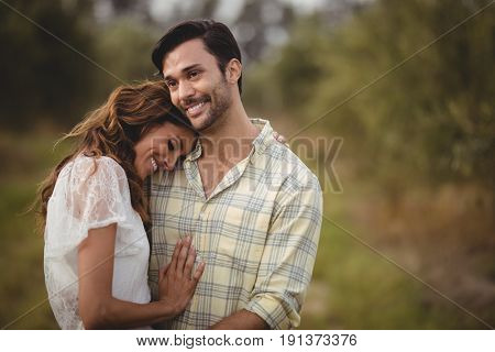 Smiling young couple embracing at olive farm