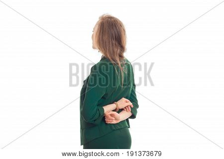 young blonde in green jacket stands back to camera hands clasped behind their backs is isolated on a white background