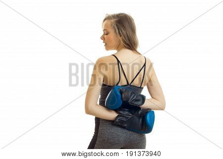 young blonde stands back to the camera and holds her arms behind her back in boxing gloves is isolated on a white background