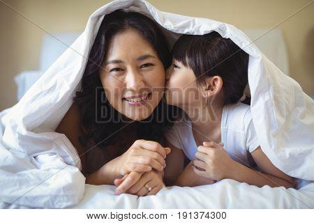 Daughter kissing her mother under blanket in bedroom at home