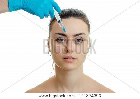 cosmetologist introduces vaccine on face of beautiful young female isolated on a white background close-up